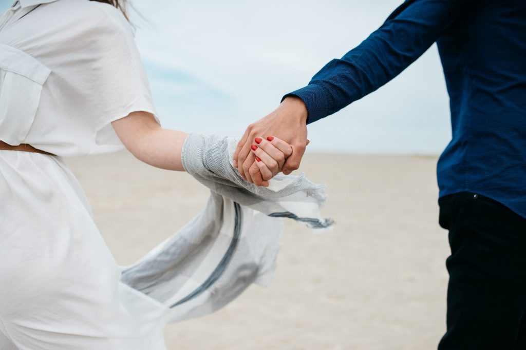 couple-holding-hands-at-the-beach