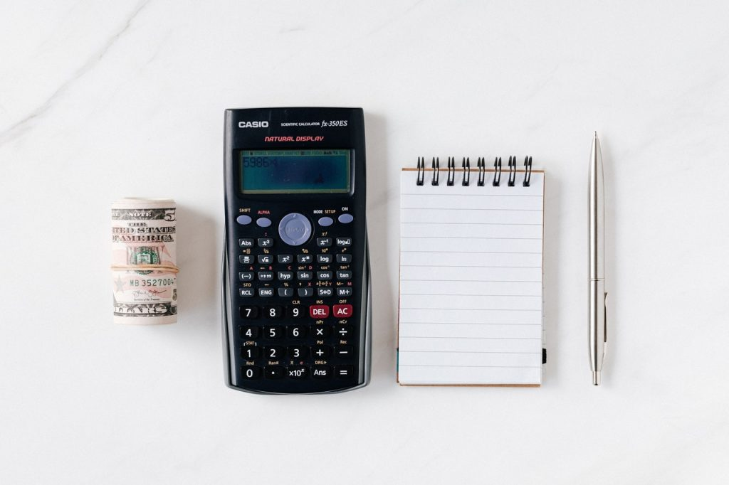 cash calculator notepad and pen on a table