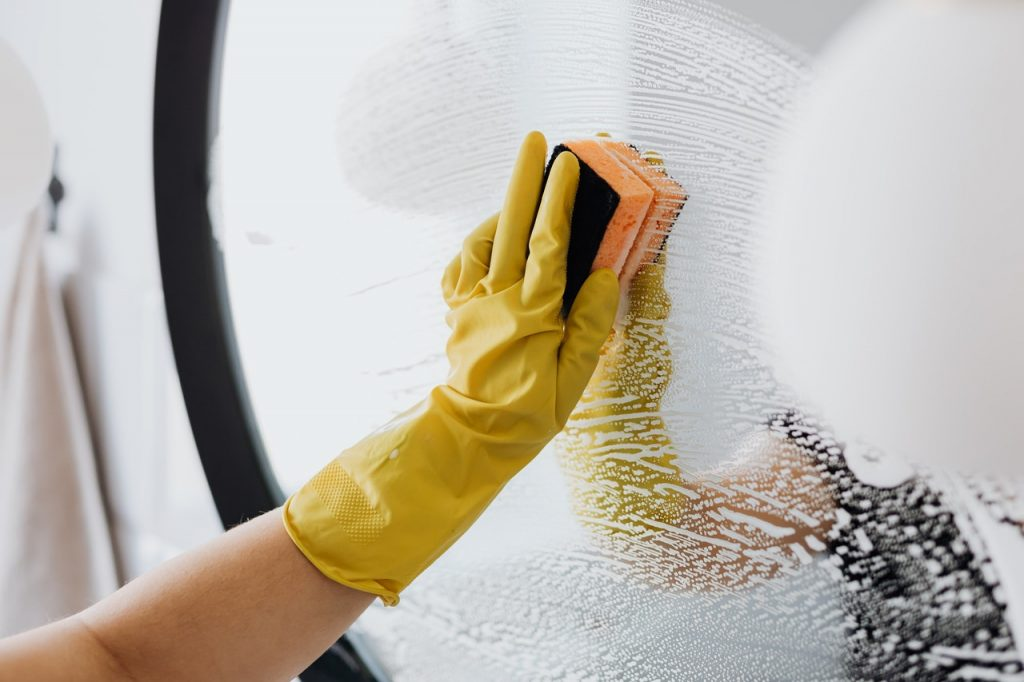 person cleaning a mirror
