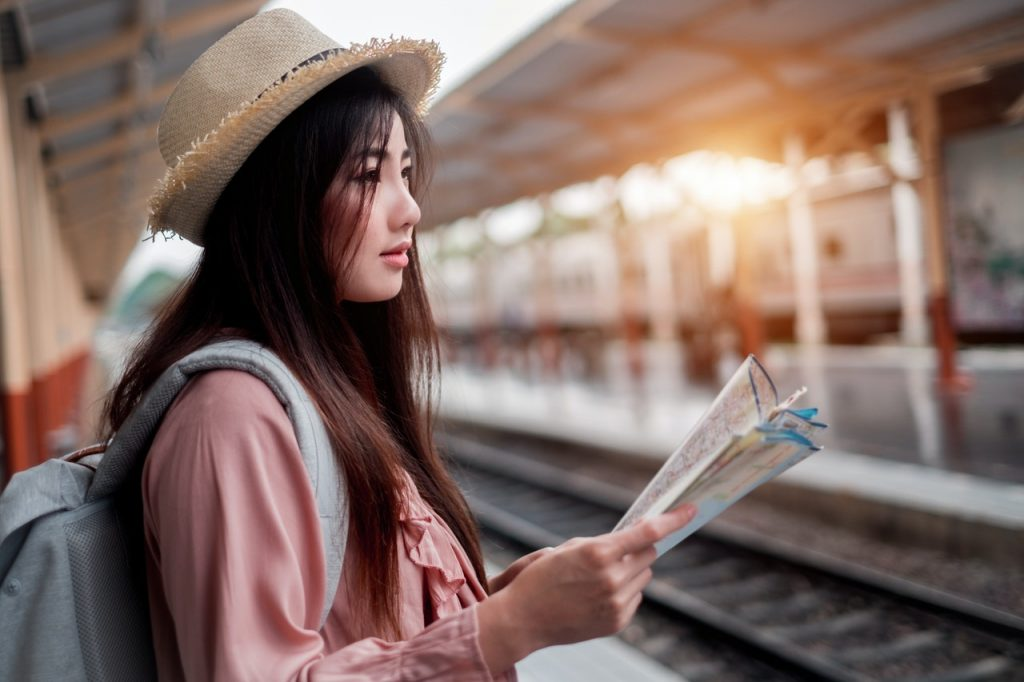 woman holding map while waiting for train
